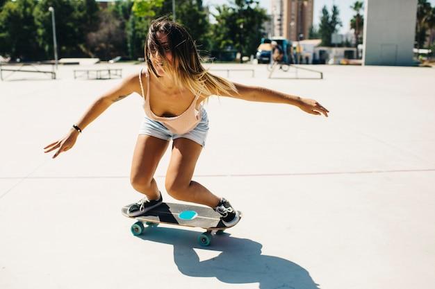 Cool femme faisant du skateboard dans la rue