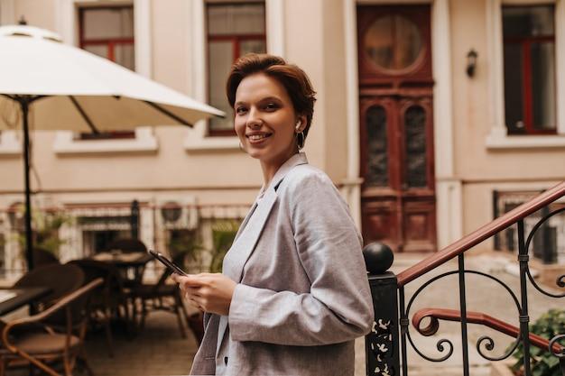 Cool femme regarde dans la caméra et tient la tablette. joyeuse dame aux cheveux noirs en veste grise élégante sourit largement et pose dans la cour