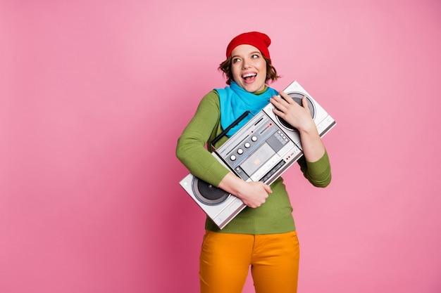 Cool fou énergique fille hug boombox profiter de jouer de la musique rétro look copyspace se réjouir crier porter pantalon jaune pantalon style pull tenue élégante isolé mur de couleur rose