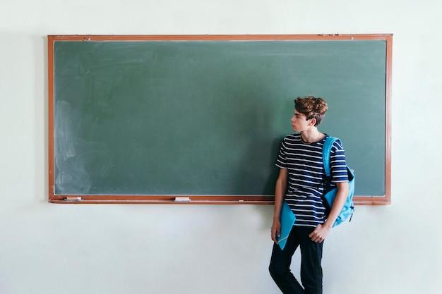 Cool garçon posant avec le tableau noir