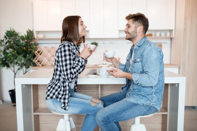Cool hipster jeune homme et femme heureux dans la cuisine, petit-déjeuner, couple ensemble le matin, souriant, prendre le thé