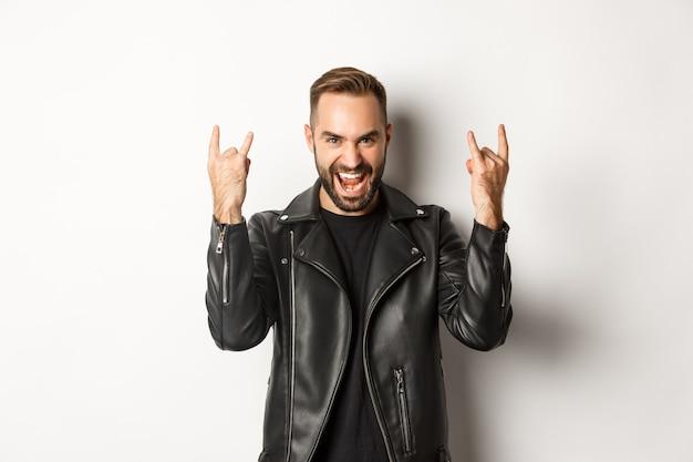 Cool homme adulte en veste de cuir noir, montrant le rock sur le geste et la langue, profitant du festival de musique, debout sur fond blanc.