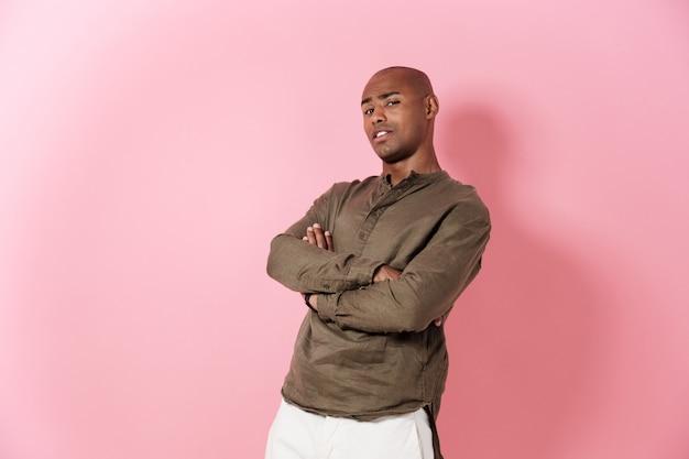 Cool homme africain posant avec les bras croisés et à la recherche