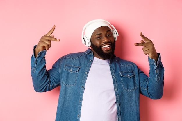 Cool homme afro-américain dansant le hip-hop, écoutant de la musique dans les écouteurs, debout sur fond rose.
