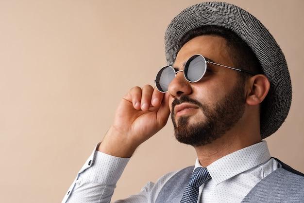Cool homme égyptien en chapeau et lunettes de soleil posant sur fond beige