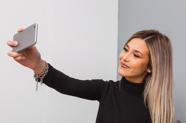 Cool jeune belle adolescente, vêtu d'un t-shirt noir, aux longs cheveux blonds, souriant, posant, prenant un selfie sur le smartphone.