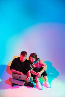 Cool jeune couple d'adolescents élégant avec un ordinateur portable néon de couleur fille et garçon blogueurs créent du contenu