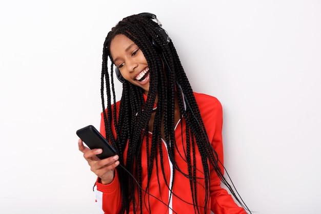 Cool jeune femme afro-américaine écoute de la musique avec casque et téléphone mobile