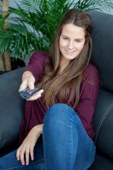 Cool jeune femme assise sur le canapé avec une télécommande