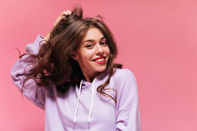 Cool jeune femme bouclée en sweat à capuche violet sourit largement