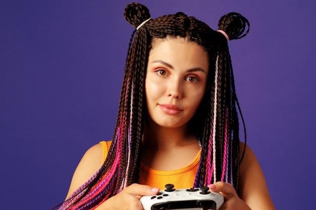 Cool jeune femme de race blanche avec des tresses colorées jouant à des jeux vidéo