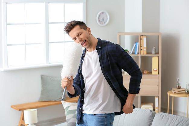 Cool jeune homme dansant et chantant tout en nettoyant son appartement