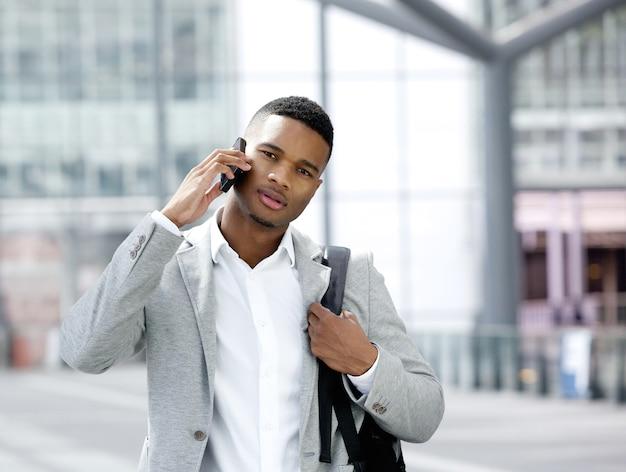 Cool jeune homme avec sac parlant sur téléphone mobile