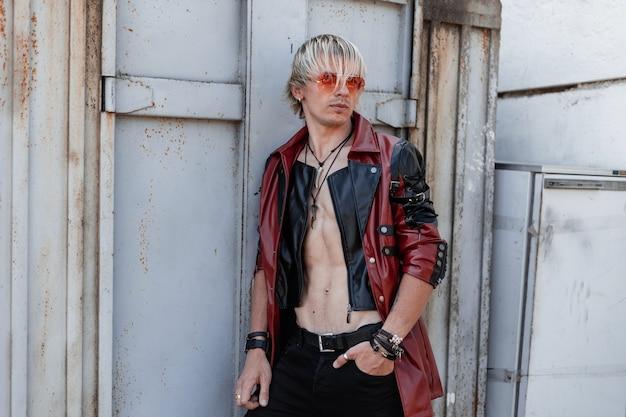 Cool jeune homme avec un torse nu avec une coiffure élégante dans une veste en cuir à la mode dans des lunettes de soleil rouges avec un jean se tient près d'un vieux bâtiment en métal gris à l'extérieur.
