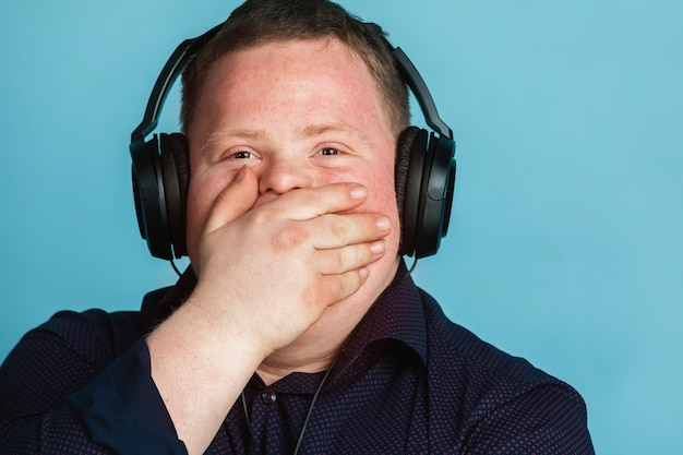 Cool jeune homme trisomique écoutant un podcast sportif