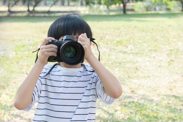 Cool petit garçon tenant un appareil photo numérique