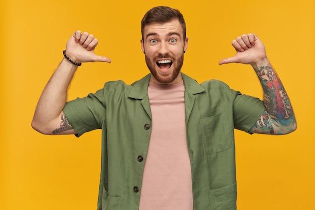 Cool à la recherche de gars masculin et gai avec des cheveux bruns et une barbe. vêtu d'une veste verte à manches courtes. a des tatouages. pointant les pouces vers lui-même. isolé sur mur jaune