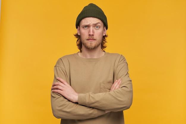 Cool à la recherche de mâle, mec barbu perplexe avec une coiffure blonde. porter un bonnet vert et un pull beige. garde les bras croisés. isolé sur mur jaune