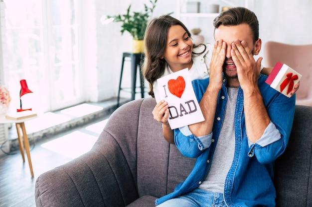 Cool surprise de ma fille. je t'aime papa. beau jeune homme à la maison avec sa petite fille mignonne. joyeuse fête des pères