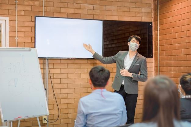 Coopération commerciale : un jeune entraîneur ou conférencier asiatique fait une présentation sur un tableau à feuilles mobiles à divers hommes d'affaires lors d'une réunion au bureau. un tuteur ou un formateur masculin présente le projet à divers collègues.