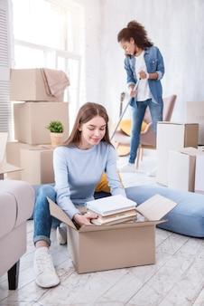 Coopération fructueuse. charmante étudiante déballant une pile de livres pendant que sa colocataire nettoie leur nouvelle chambre partagée dans le dortoir