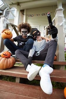 Copains avec des costumes d'halloween assis dans les escaliers