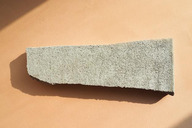 Copeaux de béton sur un fond de papier beige dans une lumière intense avec des ombres. mise en page à plat, vue de dessus.