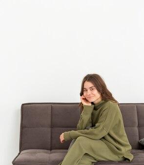 Copie-espace jeune femme assise sur un canapé