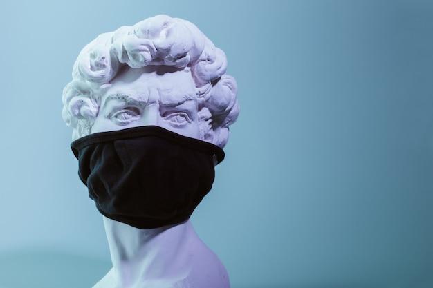 Copie en plâtre de la sculpture david michelangelo dans un masque médical noir réutilisable