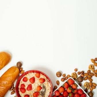 Copier de la bouillie avec des fraises et arrangement de noix sur fond uni