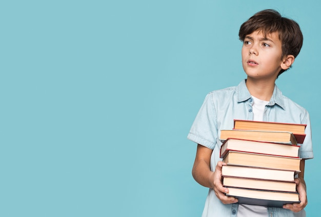 Copier l'espace jeune garçon tenant des livres