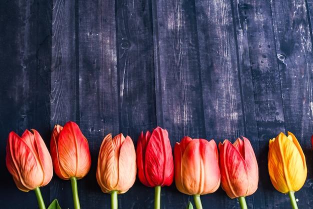 Copiez le bouquet de l'espace de tulipes orange et jaunes sur une table en bois rustique