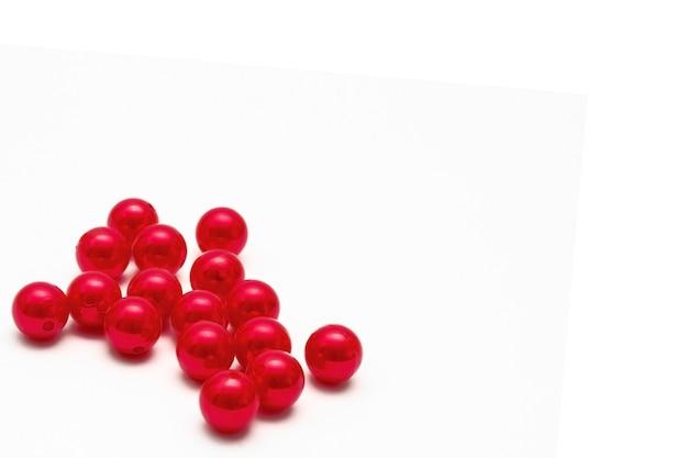 Copiez l'espace, des perles rouge vif sur fond blanc avec un espace pour l'inscription.