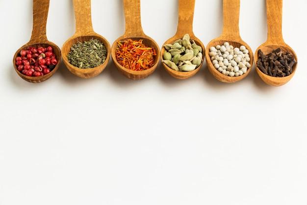 Copiez l'espace variété d'épices dans des cuillères en bois