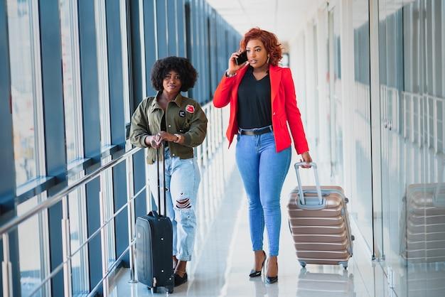 Copines afro-américaines voyagent en avion le concept de transport aérien et de loisirs à l'étranger