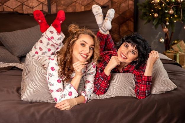 Copines allongées sur le lit en pyjama. ils sourient et célèbrent le nouvel an et noël. il y a des cadeaux et des branches de sapin décorées avec des boules dorées.