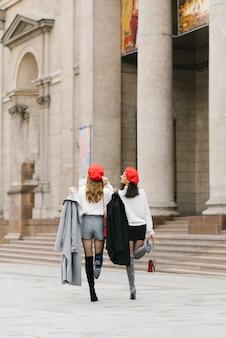 Des copines en bérets rouges font le tour de la ville et marchent, rient et profitent de la vie.