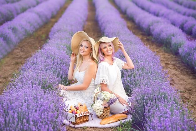 Copines blondes s'assoient dans un champ de lavande. pique-nique à la lavande. croissants et petits pains dans le panier.