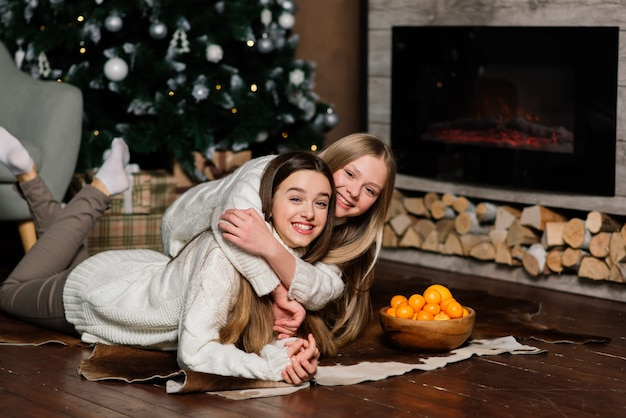 Copines célébrant le nouvel an et noël et mangeant des mandarines sur le lit. il y a des cadeaux et des branches de sapin décorées avec des boules d'or.