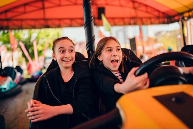 Copines dans un parc d'attractions conduisant une auto tamponneuse