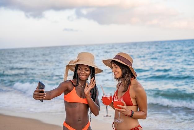 Copines faisant un appel vidéo sur la plage