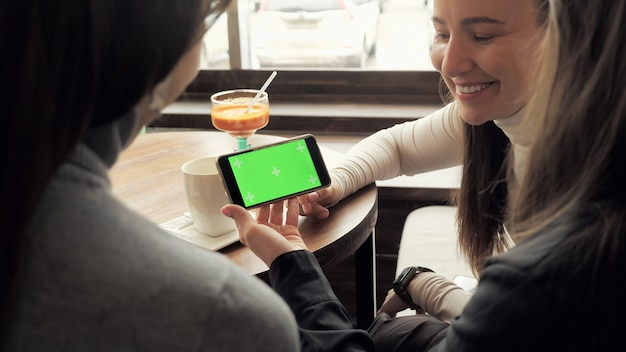 Les copines de femmes regardent l'écran vert dans le smartphone et en parlent assis dans un café. rencontre amicale au café.