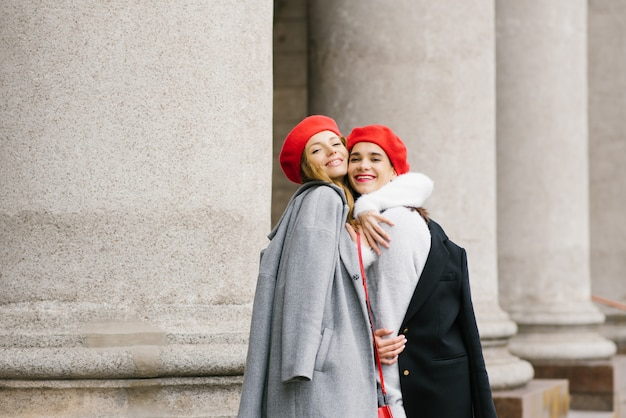Copines heureuses et souriantes s'embrassent dans la ville en automne ou au début du printemps.