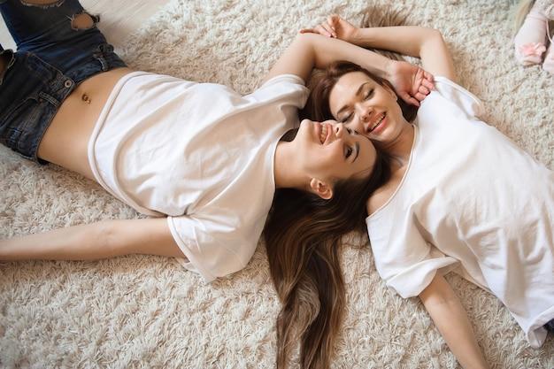 Copines heureux couché sur les sœurs de vue de dessus arrière.