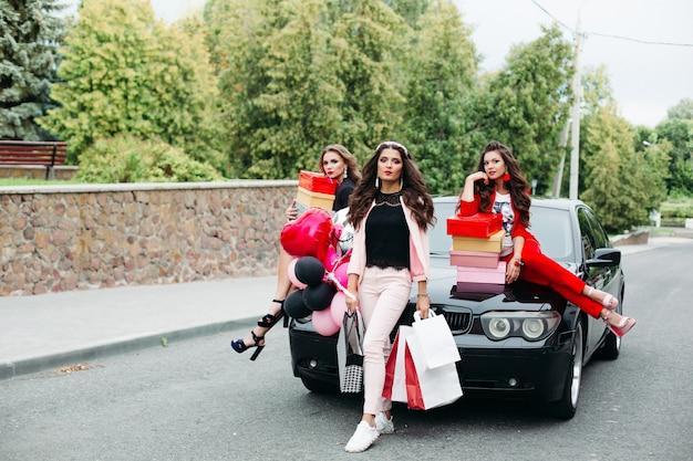 Copines à la mode avec des sacs à provisions et des boîtes sur une voiture cool.