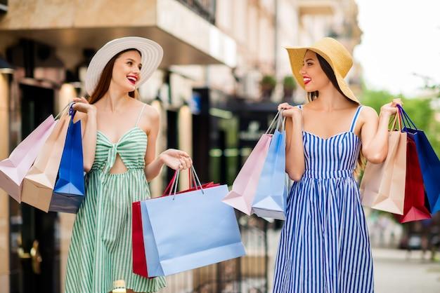 Copines en robes d'été et chapeaux de paille posant ensemble