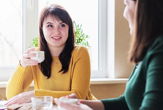 Copines s'asseoir buvant du café et bavardant