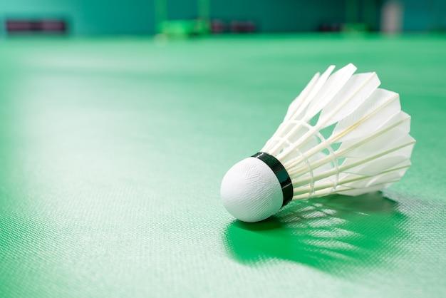 Coq navette blanc de badminton et éclairage au néon sur un sol vert