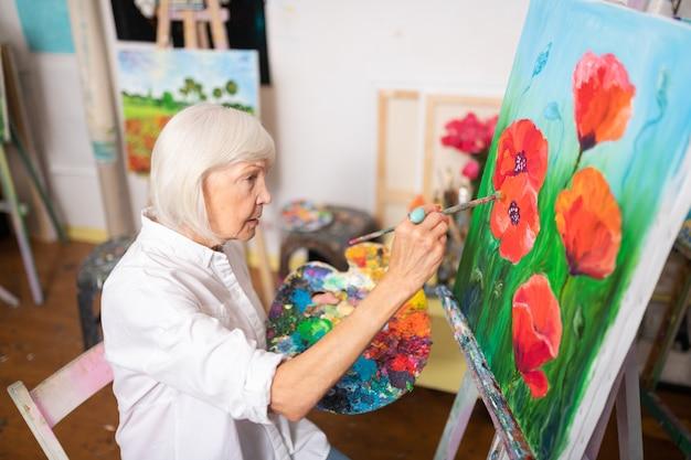 Coquelicots sur toile. retraité talentueuse aux cheveux blonds peignant des coquelicots rouges sur toile
