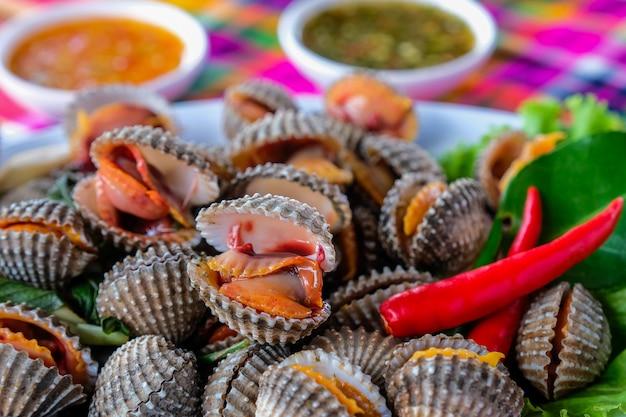 Coques fraîches bouillies sur un légume de laitue pour servir des fruits de mer